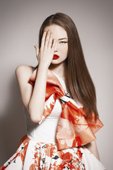 young beautiful asian brunette in gorgeous dress cover one eye