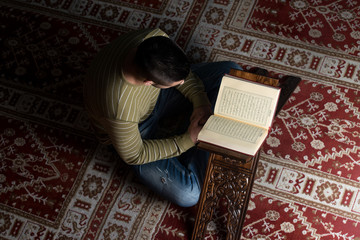 Young Muslim Guy Reading The Koran
