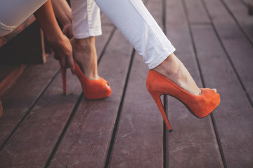 girl try on beautiful  orange shoes