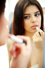 Young woman looking at mirror while doing makeup