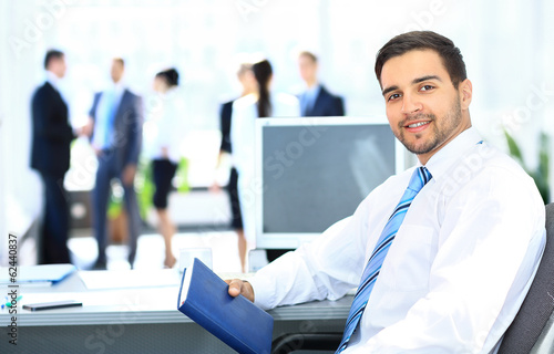 Portrait of smiling businessman working in office