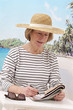 relaxed woman with hat  sitting on beach doing crossword
