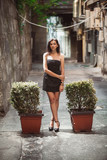 young woman in dress posing on street between bushes
