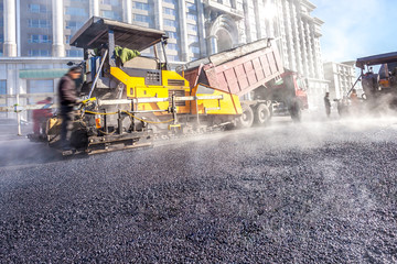 Workers making asphalt with shovels at road constructio