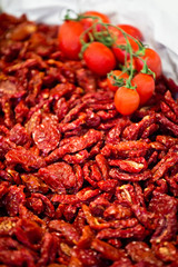 Heap of sundried tomatoes with fresh tomatoes on the vine