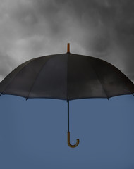 Umbrella with heavy clouds above and clear blue under