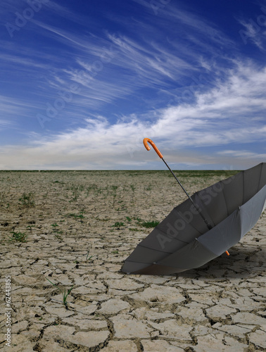 Dry deserted landscape with open black umbrella.