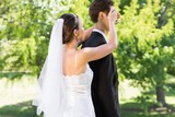 Young bride covering eyes of groom in garden