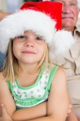 Girl wearing Santa hat at home