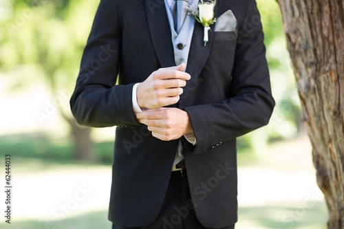 Groom adjusting sleeve in garden