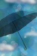 Umbrella on blue background with bokeh and clouds