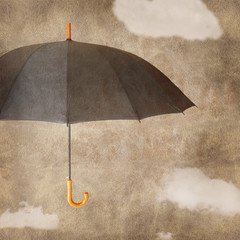 Fun umbrella on brown grungy background with clouds