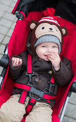 happy baby boy sitting in a red stroller