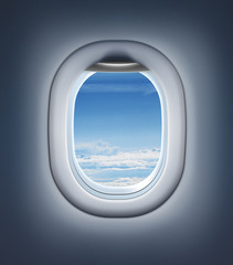 Airplane interior or jet window with clouds and sky.