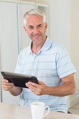 Smiling man using his tablet at breakfast