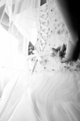Black and white photo of bride tying corset on wedding dress