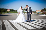 Newly married couple holding hands and walking on crosswalk