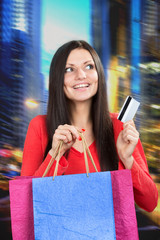 Smiling girl with a credit card and paper bags in her hands