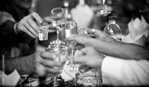 photo of hands clinking glasses with vodka at party - 62445847