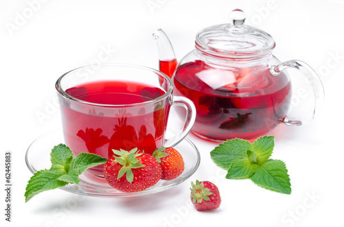 kettle and a cup of red tea with strawberries and mint isolated