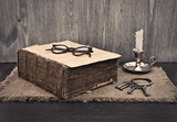 old book, glasses and a bunch of keys on wooden background