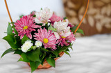 Beautiful bouquet of colorful flowers in basket against the bed