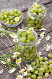 Fresh gooseberries in glass jars