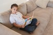 Side view portrait of a girl reading storybook on sofa