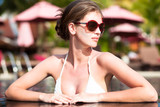 Hot young woman in sunglasses in luxury pool