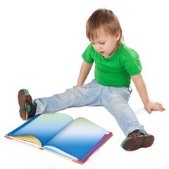 Little boy with a book sitting on the floor