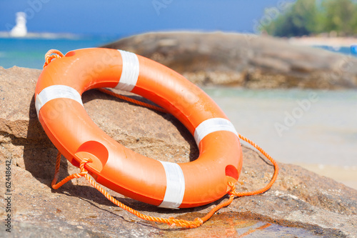 Orange lifebuoy on rocks at sea side. lifesaving equipment.