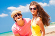Closeup of happy young couple in sunglasses on beach smiling