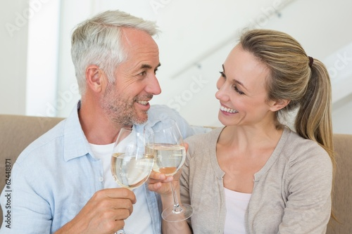 Happy couple sitting on couch toasting with white wine