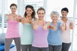 Women gesturing thumbs up in the yoga class