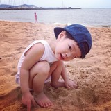 a boy wearing a cap on the beach