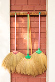 Brooms hang on wall.