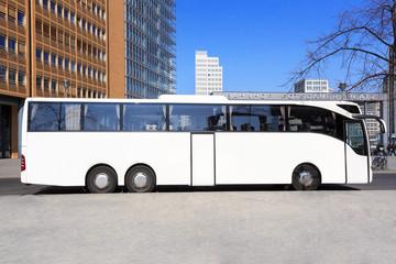 Weisser Reisebus vor Stadt-Skyline