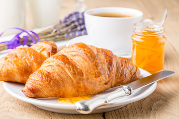 Croissants with orange jam and coffee. Shallow depth of field.