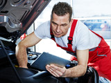 Mechanic inspecting the engine of a car with touchpad
