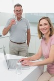 Woman using laptop while man drinking water in kitchen
