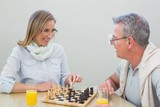 Couple playing chess while having orange juice
