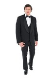 Groom in tuxedo walking over white background