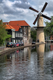 Traditional Dutch large stone windmill on the river bank