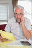 Serious mature man with home bills and calculator
