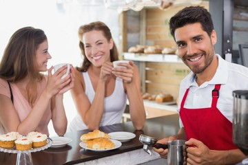Women drinking coffee with male barista at coffee shop counter