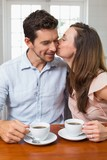 Loving couple with coffee cups at home