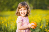 Little smiling girl with orange in a summer field