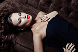 sensual elegant young woman in black dress on sofa indoor shot