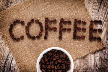 "Coffee beans as a word ""Coffee"" on a burlap. Wooden background"