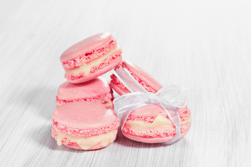 Pink French macarons on a wooden background.